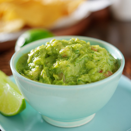 dips: guacamole in colorful blue bowl with tortilla chips Stock Photo