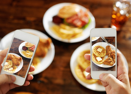 two friends taking photo of their food with smartphones Фото со стока