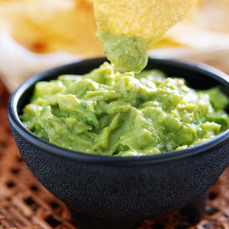 dipping tortilla chip in guacamole inside molcajete photo