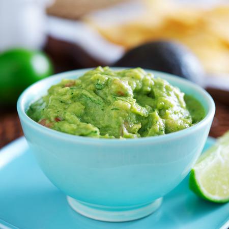guacamole in kleurrijke blauwe kom met tortilla chips Stockfoto