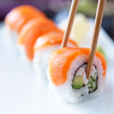 eating sushi with chopstricks photo