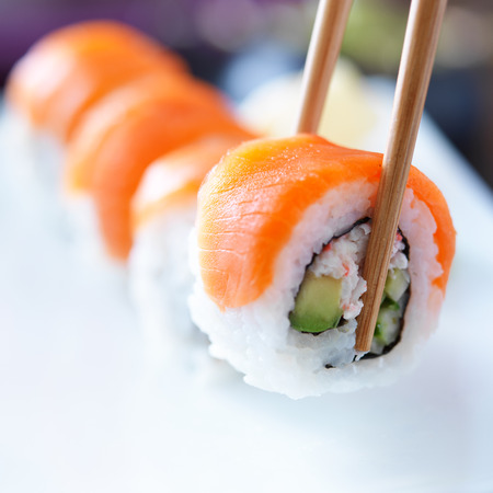 picking up a piece of sushi with chopsticks