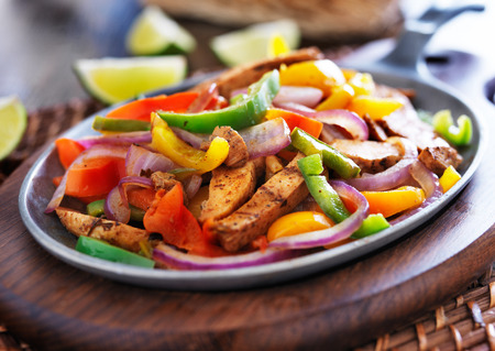 spicy chicken: mexican chicken fajitas in iron skillet with peppers