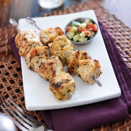 shishkabab: two grilled chicken sishkabobs with cucumber salad