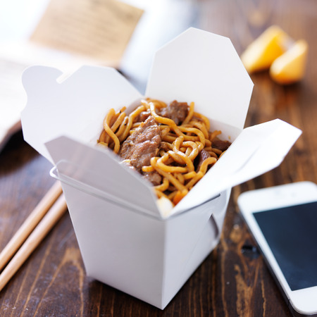 chinese take out with smart phone on table and menu photo