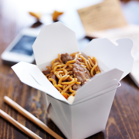 close up food: chinese take out with smart phone on table and menu