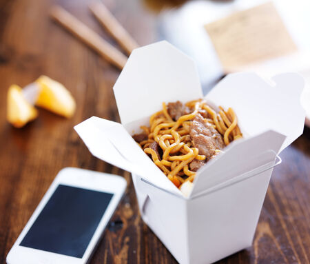 take out: chinese take out with smart phone on table and menu