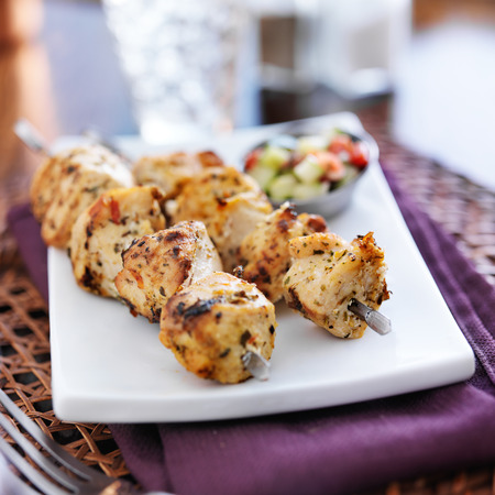 two grilled chicken skewers with cucumber salad photo