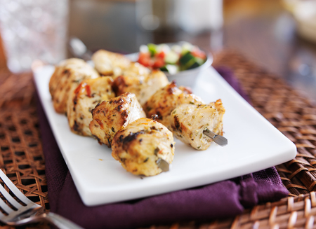two grilled chicken kabab with cucumber salad