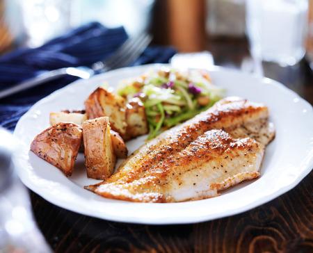 pescado frito: pan tilapia frita con ensalada asiática y patatas asadas Foto de archivo