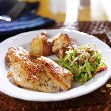 fried fish: pan fried tilapia with asian slaw and roasted potatoes Stock Photo