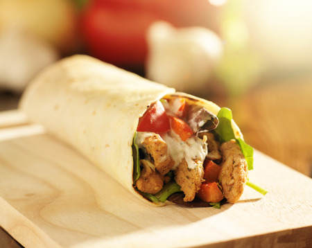chicken wrap in tortilla with sauce and mesclun mix Stock Photo