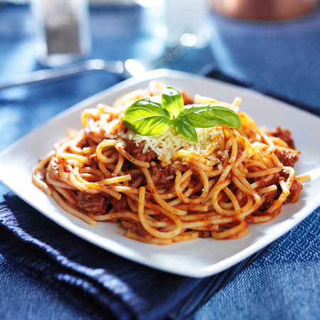 spaghetti in bolognese sauce with basil garnish photo