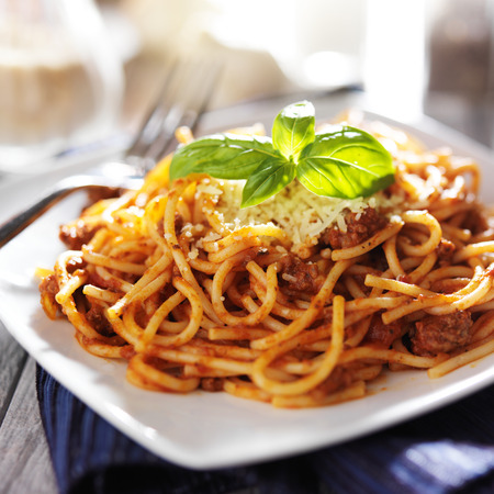 spaghetti in bolognese sauce with basil garnish