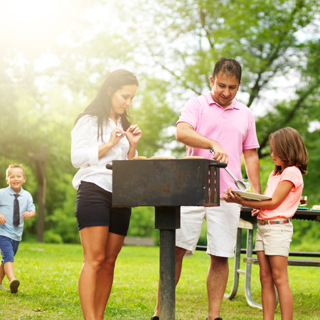 food getting served at family barbecue while children play photo