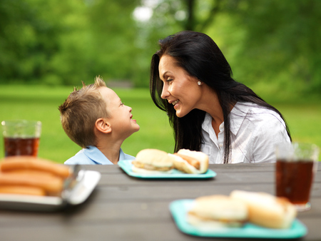 a little dinner: mother and son at picnic in park Stock Photo