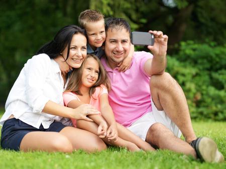 famille: famille prenant selfies smartphone dans le parc