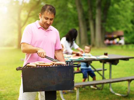 grill: father grilling hot dogs and bratwurst for family at barbecue Stock Photo