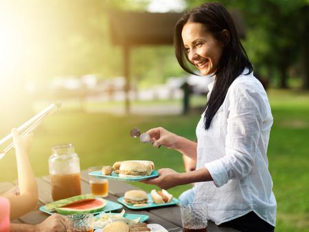 moeder eten serveren bij cookout barbecue in park