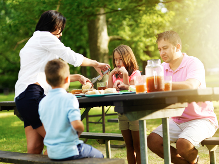 familia pic nic: familia de cuatro personas comiendo en cookout de la barbacoa
