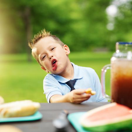 making faces: bambino a fare picnic facce mentre mangiare cibo Archivio Fotografico