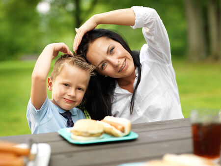 mother and son making heart shape at picnic photo