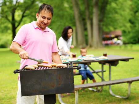 father grilling hot dogs and bratwurst for family photo