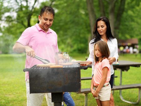 dad grilling food for wife and kids at outdoor cookout photo