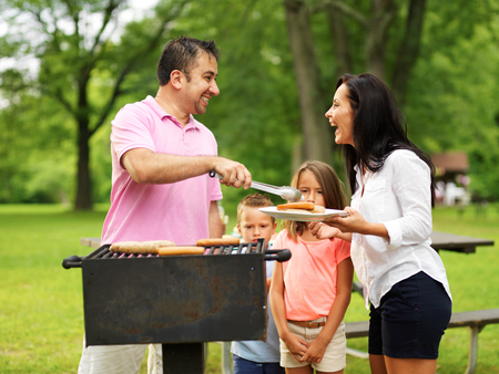 grill: family cookout - dad giving mom food on platter from grill Stock Photo