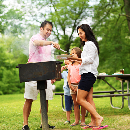 family barbecue - dad giving wife cooked food photo