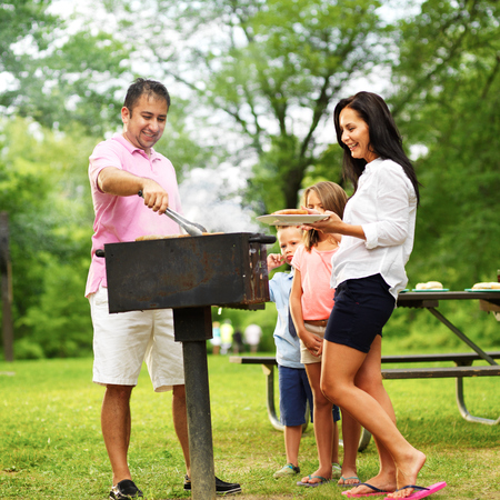 dad dishing out cooked food at family cookout Stock Photo