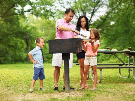 family barbecue - dad giving kids food Archivio Fotografico