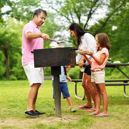 kids food: family barbecue - dad giving kids food Stock Photo