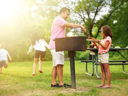 La nourriture pour se faire servir au barbecue de la famille tandis que les enfants jouent Banque d'images - 31526124