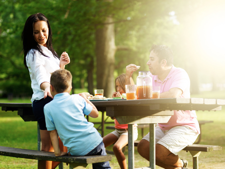 eating: family of four eating at barbecue cookout Stock Photo