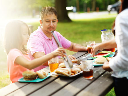 father and daughter eating together at barbecue cookout photo