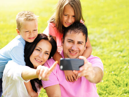 family taking selfies with smartphone in park photo
