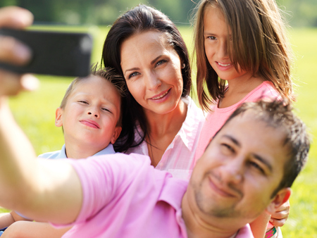 father taking selfie with family photo