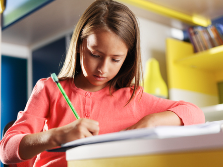 concentrating: child concentrating on homework in bedroom Stock Photo