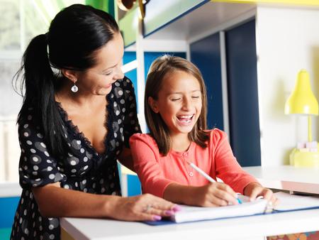 niños escribiendo: madre ayudando a su hija feliz con la tarea