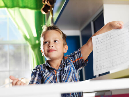 cute little boy showing his completed homework photo