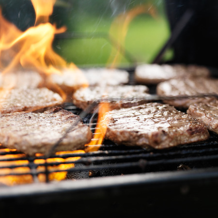 grilling hamburgers on charcoal grill with flames photo