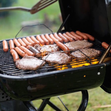 turn over: turning food on grill with haumbers and hotdogs Stock Photo