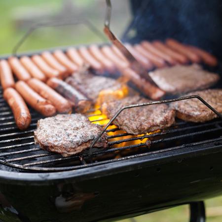 perro caliente: parrilla llena de perritos calientes y hamburguesas para cocinar Foto de archivo