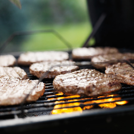 staycation: hamburgers grilling on charcoal grill