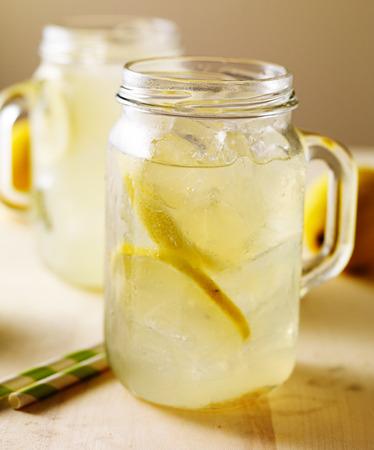jar of fresh homemade lemonade on wood table photo