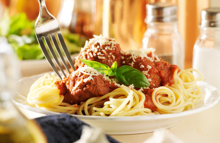 eating spaghetti and meatballs with fork