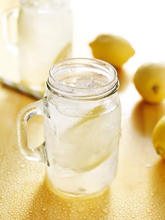 vasos de agua: limonada casera en tarro de alba�il con la paja a un lado