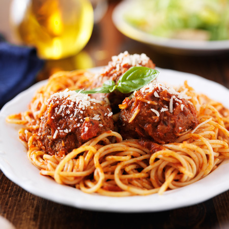 cluttered: spaghetti and meatballs at cluttered dinner table