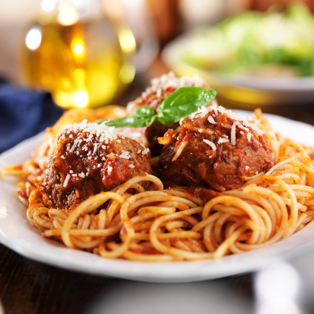 spaghetti and meatballs at cluttered dinner table photo